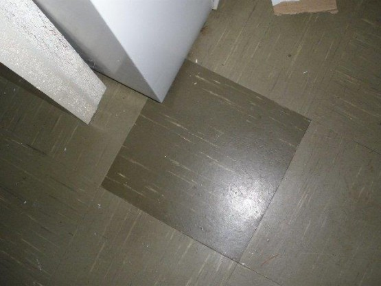 Olive Green Asbestos Floor Tiles with a darker coloured tile in the middle.