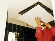 Man working on Ceiling Tiles Asbestos Insulation Board