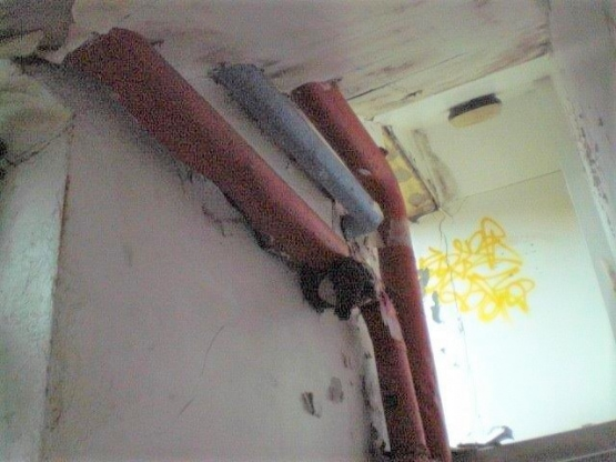 Asbestos Pipe Lagging on the wall of the stairs.